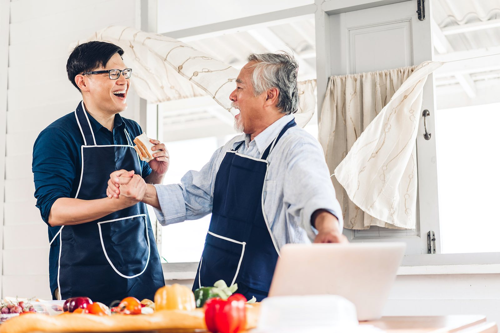 Father and older son laughing in the kitchen